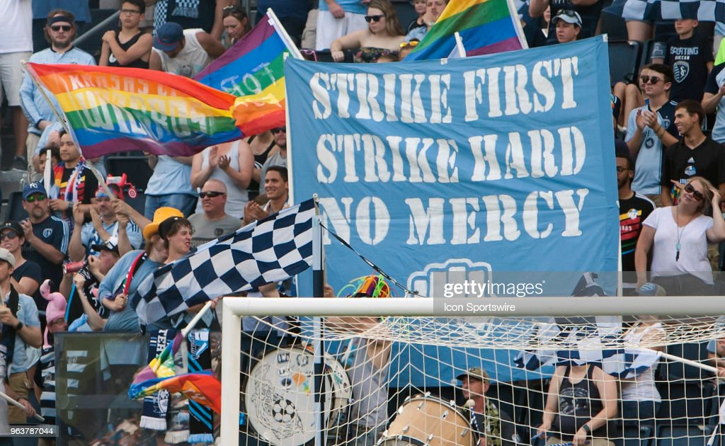 Members of the South Stand supporters group hold a two pole tifo along in waving flags during the MLS regular season match between Sporting Kansas City and the Columbus Crew on Sunday May 27th, 2018 at Children's Mercy Park in Kansas City, KS.