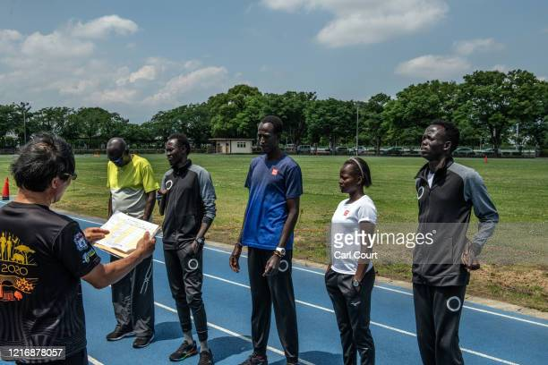 Members of the South Sudanese Olympic team listen to instructions from Japanese head coach Hiroshi Yoshino as they prepare to train at an athletics...