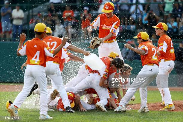 Members of the Southwest Region team from River Ridge Louisiana celebrate after getting the last out to defeat the Caribbean Region team from...