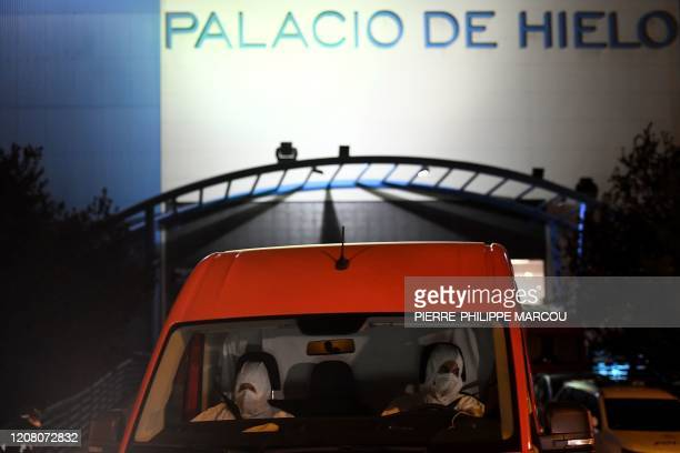 Members of the Spanish Army's Military Emergency Unit wearing protective suits drive a van outside the Palacio de Hielo shopping mall where an ice...
