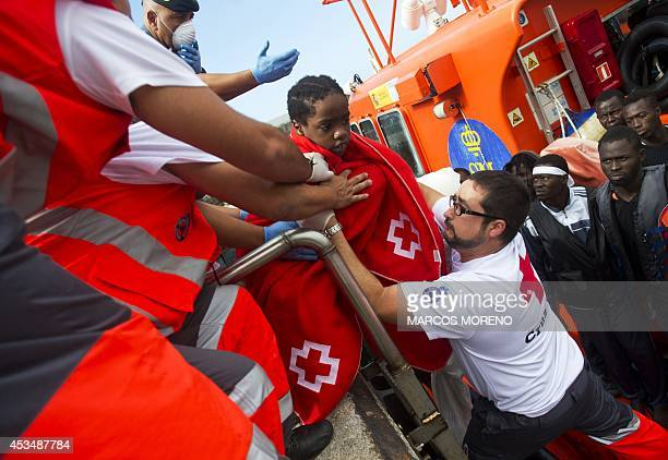 Members of the Spanish emergency services and Red Cross help a young girl to disembark a coastguard vessel at Tarifa's harbour on August 11 2014...