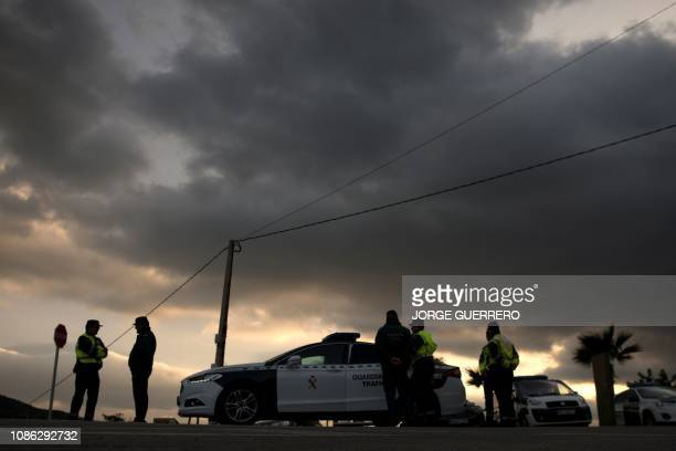 Members of the Spanish Guardia Civil stand guard at the site where a child fell down a well in Totalan southern Spain on January 22 2019 The search...