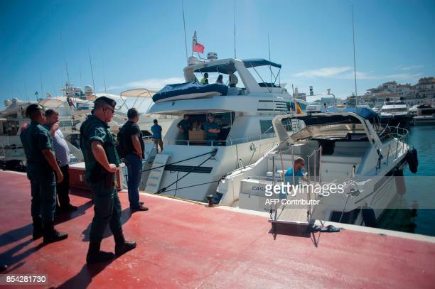 Members of the Spanish Guardia civil stand on the docks during a raid targeting the Russian mafia in the Puerto Banus marina area of the southern...