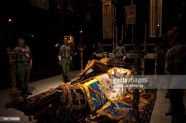 Members of the Spanish Legion guard a statue of the Christ of the Good Death before a Holy Week procession in Malaga on March 27 2013 Christian...