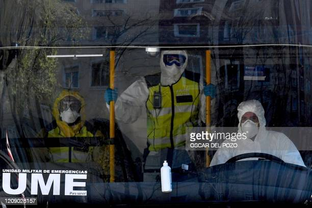 Members of the Spanish Military Emergencies Unit wearing protective suits are pictured on a bus used to transport patients from the Gregorio Maranon...