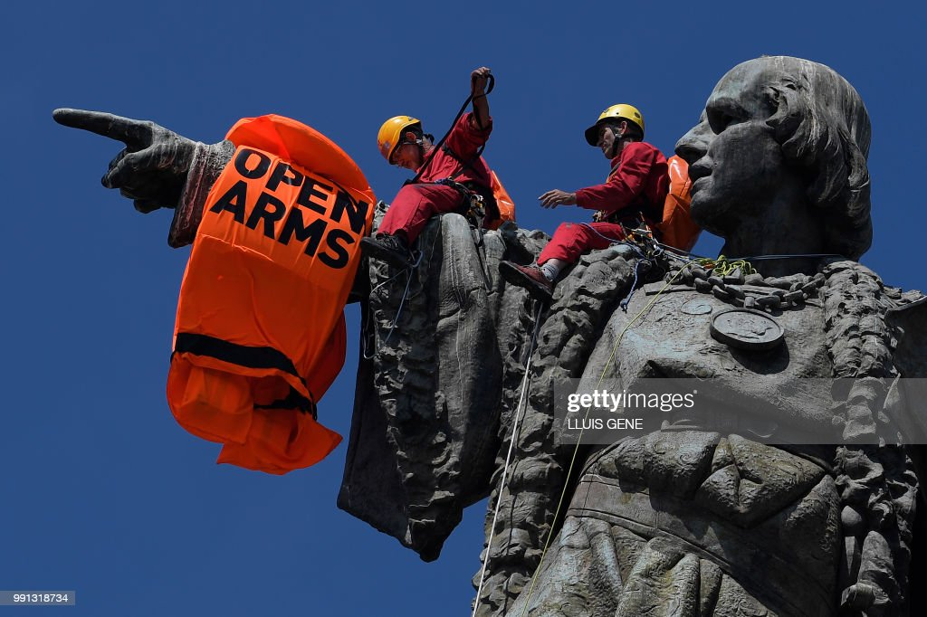 Members of the Spanish NGO Proactiva Open Arms place a lifejacket on the statue of Christopher Columbus in Barcelona on July 4, 2018, on the day that the NGO Proactiva Open Arms ship arrived with 60 migrants on board rescued as they tried to cross the Mediterranean from Libya after Italy and Malta refused access.