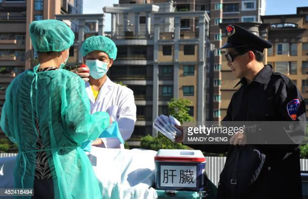Members of the spiritual movement Falungong act out a scene of stealing human organs to sell during a demonstration in Taipei on July 20 2014 against...