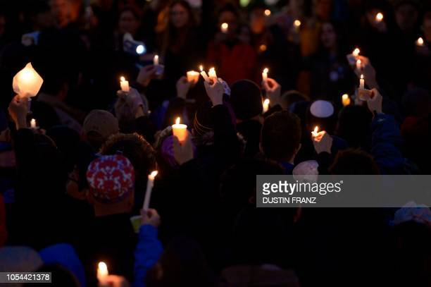 Members of the Squirrel Hill community hold up lit candles as they come together for a studentorganized candle vigil in rememberance of those who...