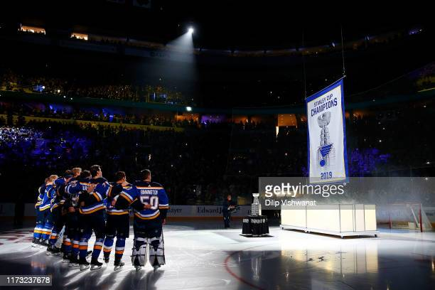 Members of the St Louis Blues watch the Stanley Cup Champions banner being raised prior to playing against the Washington Capitals at Enterprise...