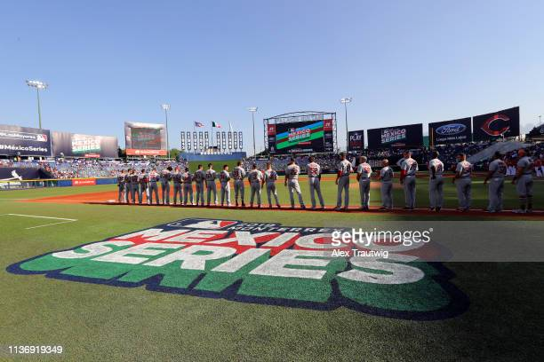 Members of the St Louis Cardinals are seen on the base path during the singing of the national anthems prior the game between the St Louis Cardinals...