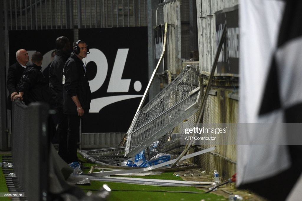 Members of the stadium staff stand by the stadium barrier that collapsed during the French L1 football match between Amiens and Lille LOSC on September 30, 2017 at the Licorne stadium in Amiens. Several Lille supporters were hurt in Amiens when a stadium barrier collapsed in the away section as the visiting fans celebrated the opening goal of the match. The Ligue 1 fixture was interrupted in the 16th minute after LOSC French defender Fode Ballo-Toure's goal sparked celebrations that caused a fence separating the fans from the pitch to crumble under their weight. PRESTI