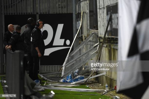 Members of the stadium staff stand by the stadium barrier that collapsed during the French L1 football match between Amiens and Lille LOSC on...