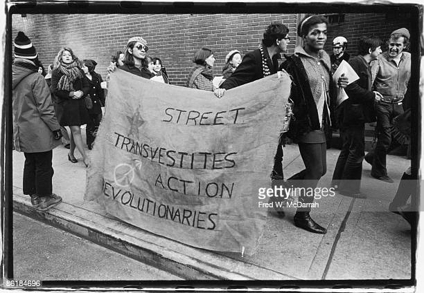 Two people carry a sign that reads 'Street Transvestites Action Revolutionaries' along a crowded sidewalk New York New York December 20 1970