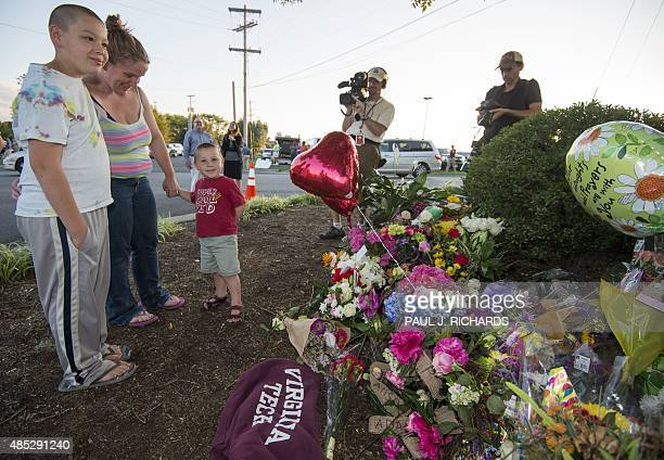 Members of the Stump family pay their respects at a makeshift memorial for reporter Alison Parker and cameraman Adam Ward at the gate of WDBJ...