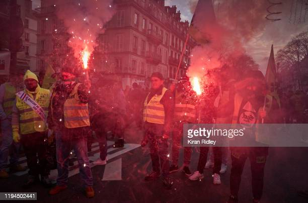 Members of the Sud Union light flares as they march through the streets of Paris in support of the National strike with new unions joining the strike...