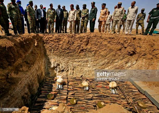 Members of the Sudanese army stand as weapons that were collected from Sudanese citizens are destroyed in the Hajar al-Asal base, the Nile River...
