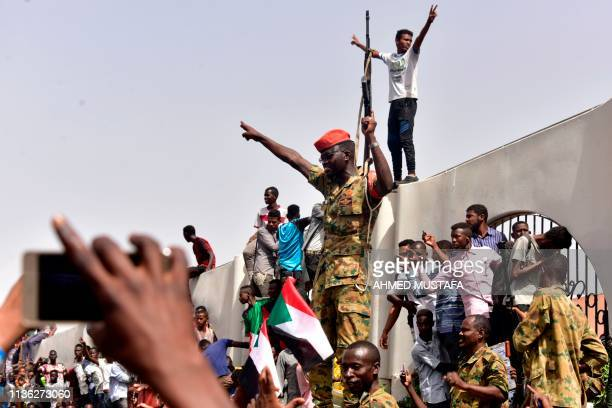 TOPSHOT Members of the Sudanese military gather in a street in central Khartoum on April 11 after one of Africa's longestserving presidents was...
