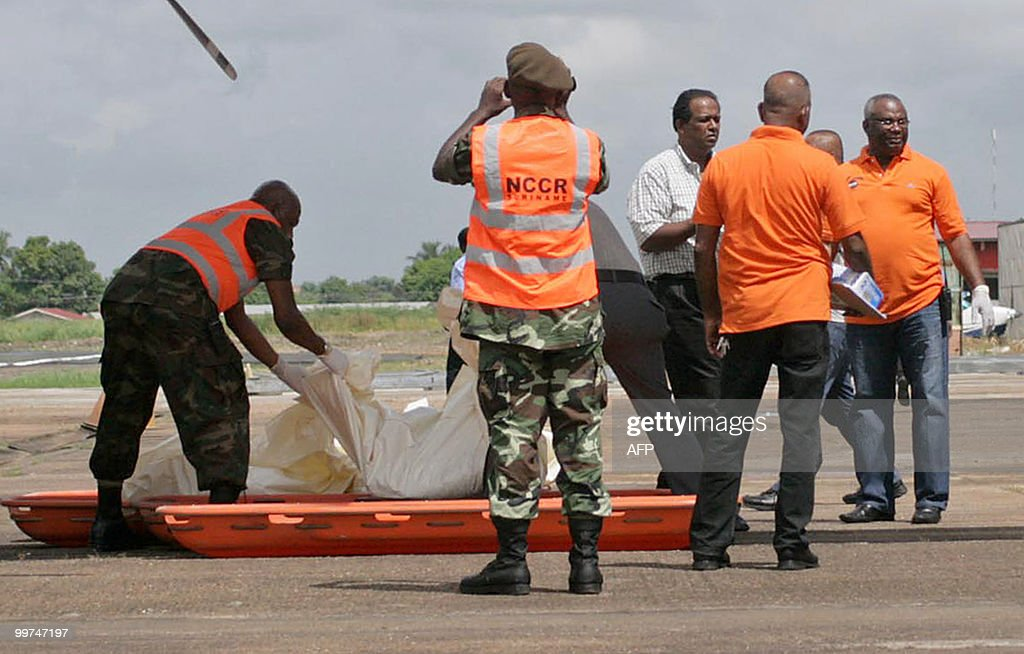 Members of the Surinam National Coordination Center for Disaster Management (NCCR) download the remains of the victims of the crashed plane, upon arrival at the Zorg en Hoop airport in Paramaribo on May 17, 2010. Eight people, including pilot and co-pilot, died in a plane crash on May 15 in the hinterlands of Suriname. This is the third accident, second with casualties, with an Antonov airplane of Blue Wing airline in two years in Surinam.