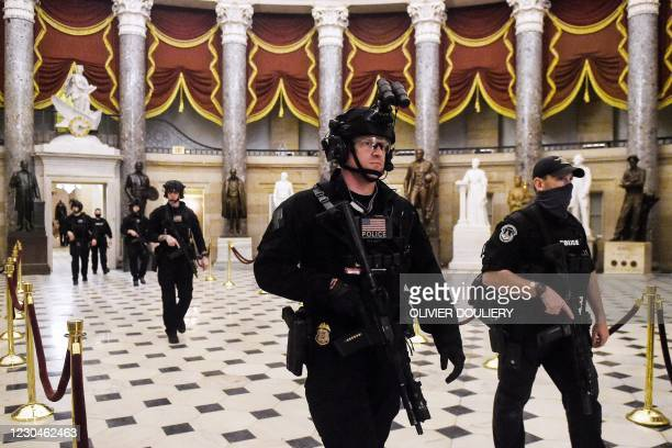 Members of the Swat team patrol and secure the Statuary Hall before US Vice President makes his way into the House Chamber, at the US Capitol, on...