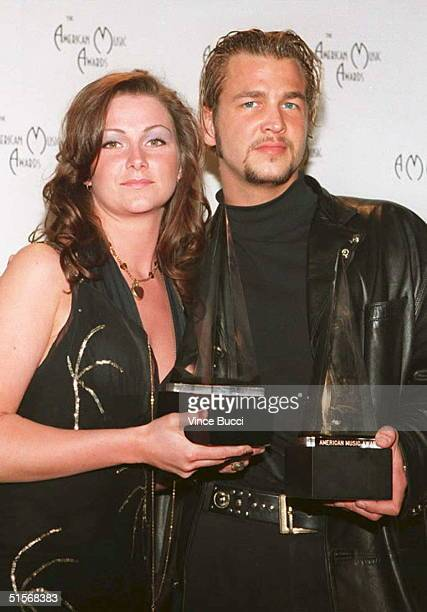 Members of the Swedish group Ace of Base Jenny Berggrem and Buddah display their trophies at the 22nd Annual American Music Awards 30 January 1995 in...