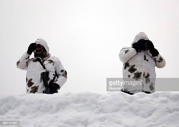 Members of the Swiss army use binoculars to look out from a rooftop overlooking the Congress Center the venue for the World Economic Forum in Davos...