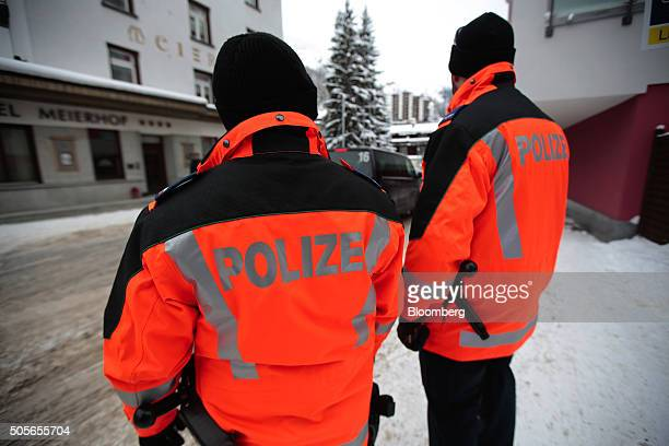 Members of the Swiss Police stand on duty near the Congress Center, venue for the World Economic Forum as a WEF shuttle bus passes along the...
