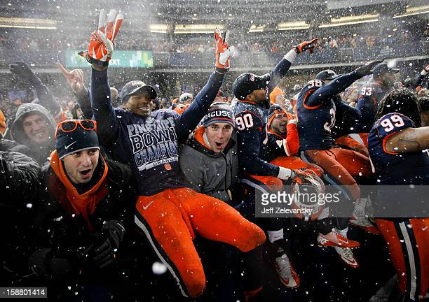 Members of the Syracuse Orange celebrate with fans after their win over the West Virginia Mountaineers in the New Era Pinstripe Bowl at Yankee...