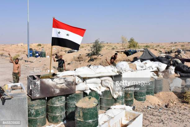 Members of the Syrain forces flash the sign for victory at a checkpoint on the outskirts of Deir Ezzor on September 10 as they continue to press...