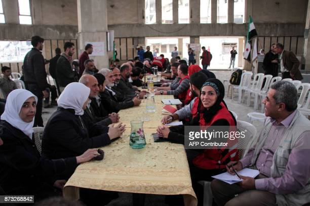 Members of the Syrian Arab Red Crescent meet with members of the local council in the town of Douma in the rebelheld Eastern Ghouta region east of...