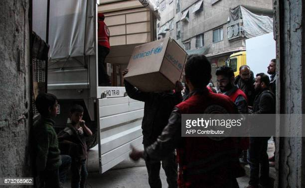 Members of the Syrian Arab Red Crescent unload humanitarian relief packages provided by the International Committee of the Red Cross in a joint...