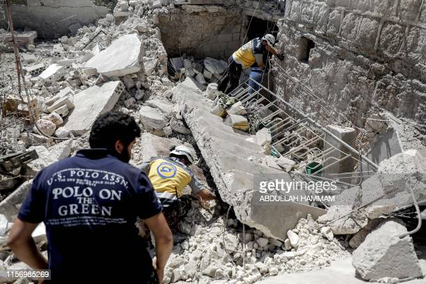TOPSHOT Members of the Syrian Civil Defence also known as the White Helmets search for bodies or survivors in a collapsed building following a...