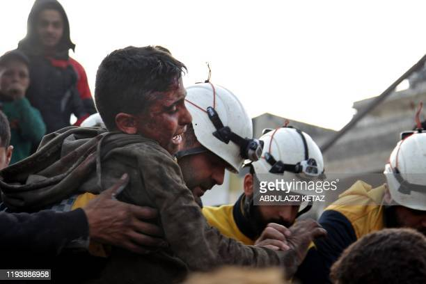 Members of the Syrian Civil Defence, also known as the White Helmets, recover a wounded boy from the rubble of a building following a regime air...