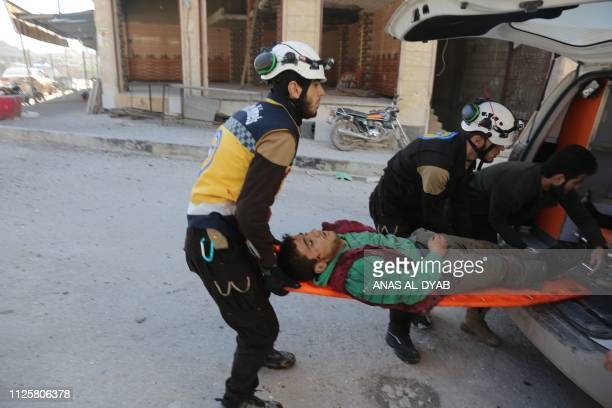 Members of the Syrian Civil Defence carry a victim after reported air strikes in the town of Khan Sheikhun in the southern countryside of the...