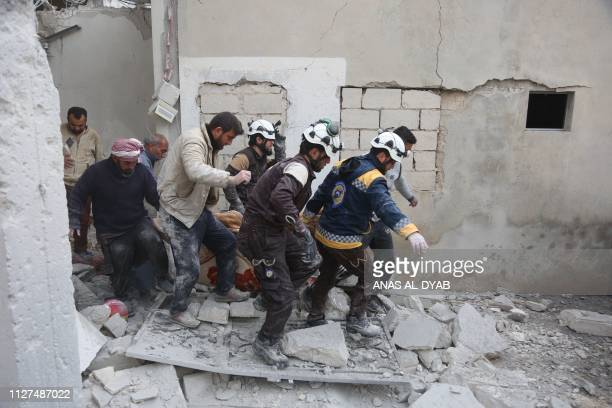 TOPSHOT Members of the Syrian Civil Defence carry a wounded person following reported shelling in the town of Khan Sheikhun in the southern...