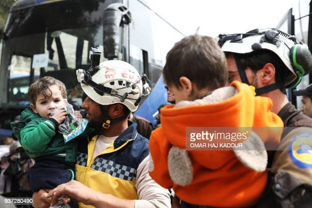Members of the Syrian Civil Defence hold children as Syrian civilians and rebel fighters arrive in the village of Qalaat alMadiq north of Hama on...