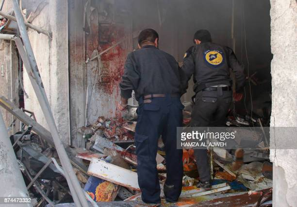 Members of the Syrian Civil Defence known as the White Helmets check a building following strikes on Douma a rebelheld town in the Eastern Ghouta...