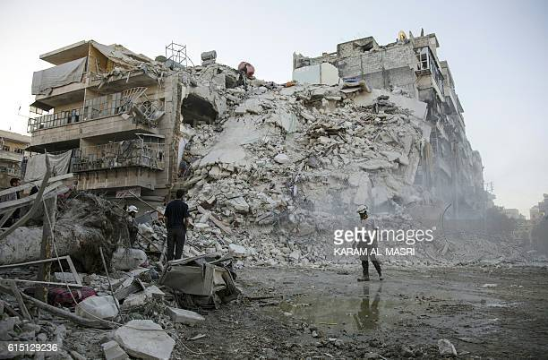 Members of the Syrian Civil Defence known as the White Helmets search for victims amid the rubble of a destroyed building following reported air...