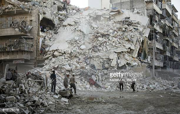 TOPSHOT Members of the Syrian Civil Defence known as the White Helmets search for victims amid the rubble of a destroyed building following reported...
