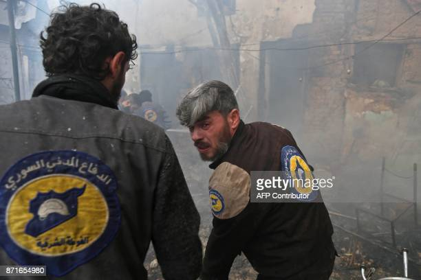 Members of the Syrian Civil Defence known as the white helmets try to extinguish flames following an air raid on the rebelheld besieged town of...