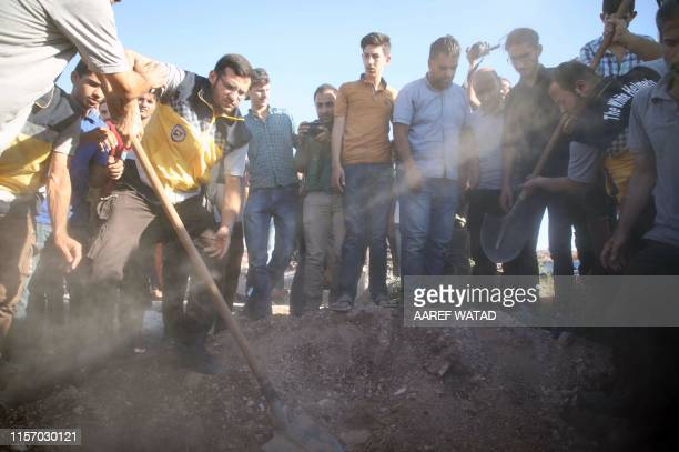 TOPSHOT Members of the Syrian Civil Defence known as White Helmets and friends bury the body of citizen journalist Anas alDyab during his funeral in...