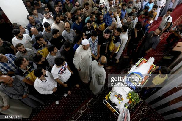 Members of the Syrian Civil Defence known as White Helmets and friends pray over the body of citizen journalist Anas alDyab during his funeral in the...