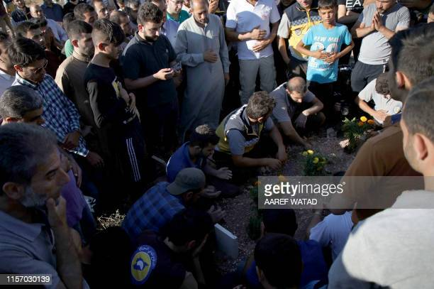 Members of the Syrian Civil Defence known as White Helmets and friends pray over the grave of citizen journalist Anas alDyab during his funeral in...
