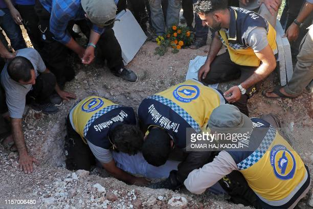 Members of the Syrian Civil Defence known as White Helmets and friends prepare to bury the body of citizen journalist Anas alDyab during his funeral...