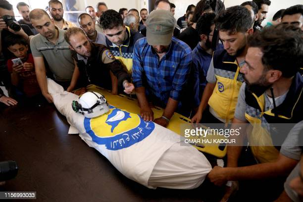 TOPSHOT Members of the Syrian Civil Defence known as White Helmets mourn over the body of citizen journalist Anas alDyab at their headquarters in the...