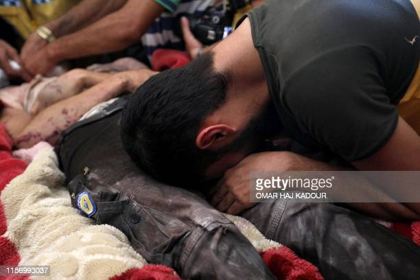 Members of the Syrian Civil Defence known as White Helmets mourn over the body of citizen journalist Anas alDyab at their headquarters in the...