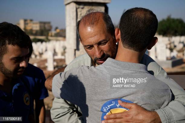 Members of the Syrian Civil Defence known as White Helmets offer their condolences to the father of citizen journalist Anas alDyab during his funeral...
