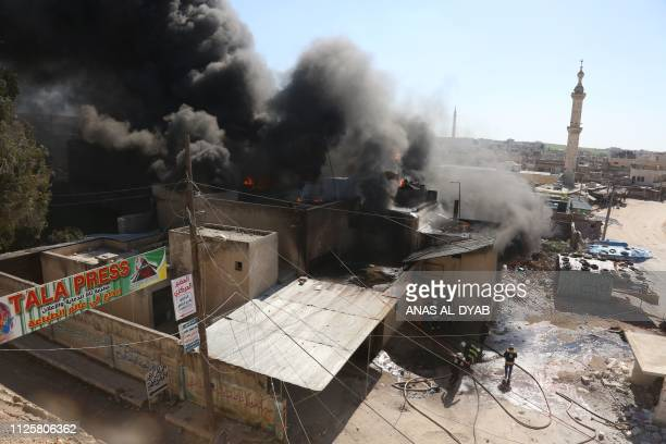 Members of the Syrian Civil Defence put out a fire at the site of reported air strikes in the town of Khan Sheikhun in the southern countryside of...