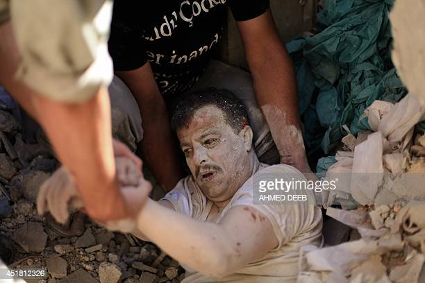 Members of the Syrian Civil Defence rescue a man under the rubble following a reported barrelbomb attack by Syrian government forces on July 7 2014...