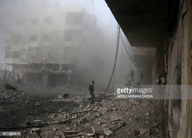 Members of the Syrian civil defence search for injured victims through the rubble of destroyed buildings in an area hit by a reported regime air...