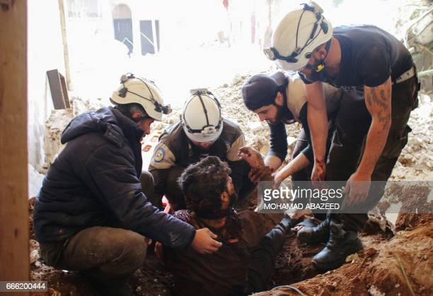 Members of the Syrian civil defence volunteers also known as the White Helmets remove a victim from the rubble of his house on April 8 following a...